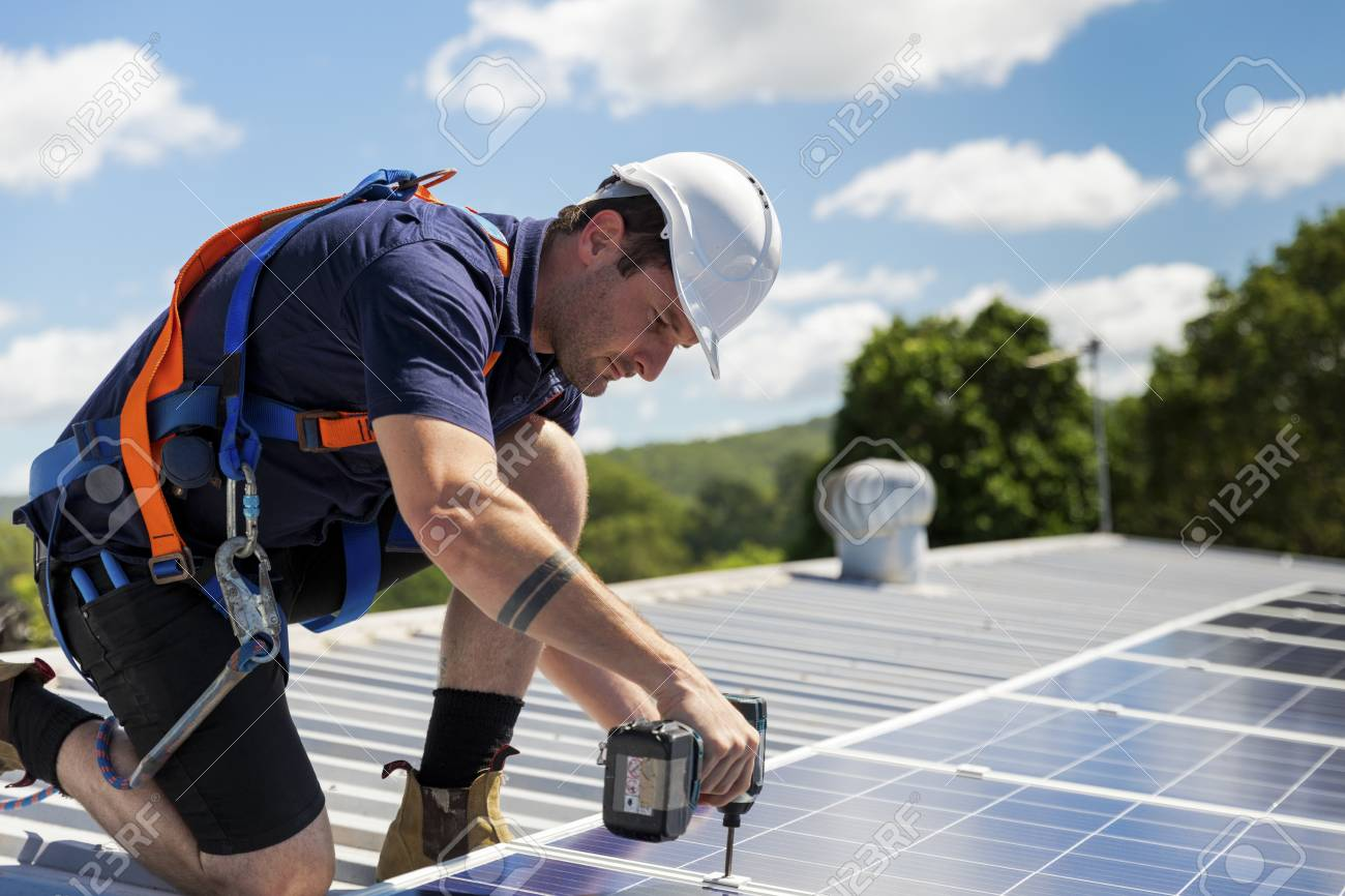 Solar panel technician with drill installing solar panels on roof on a sunny day - 99948741