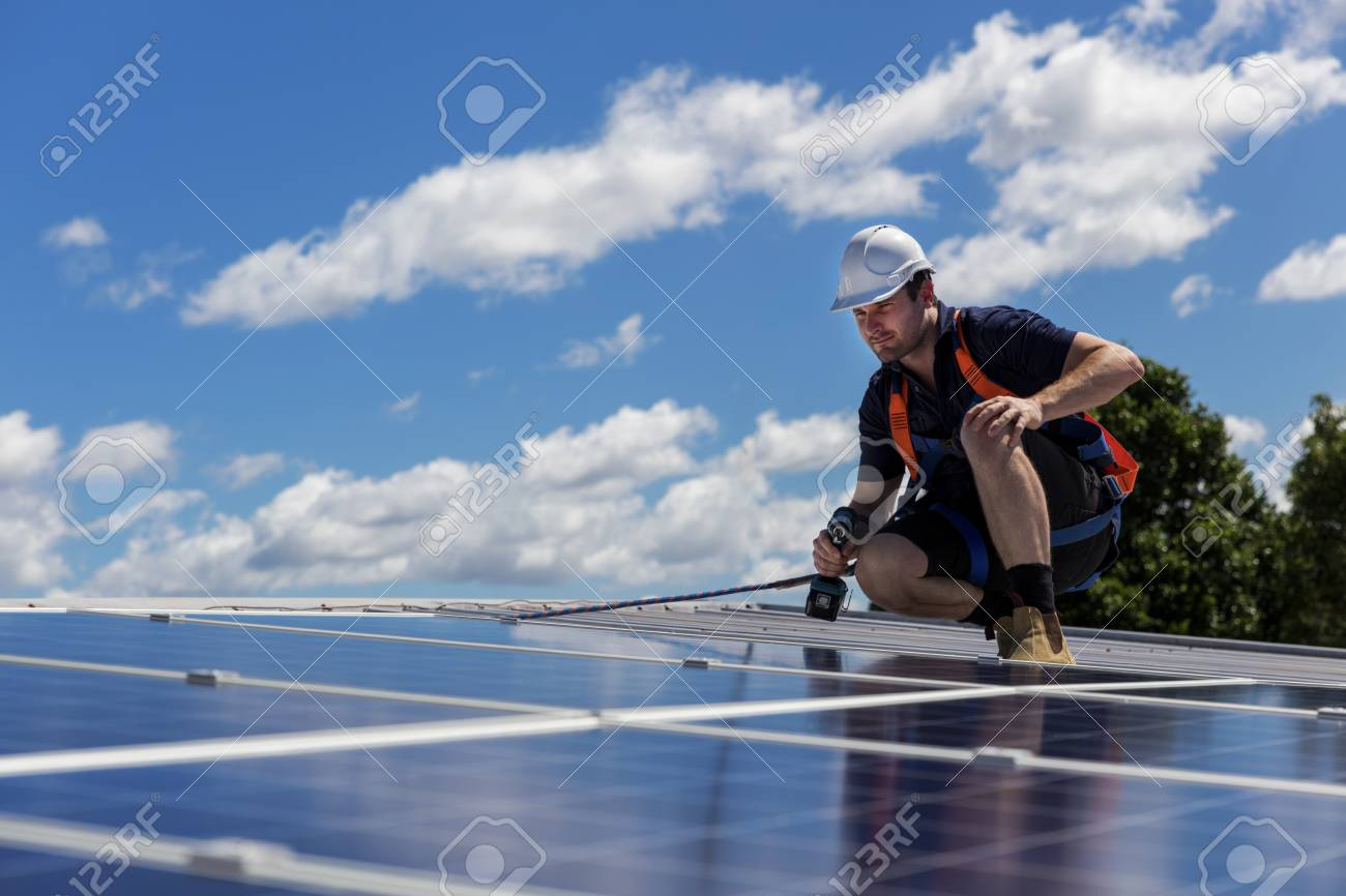 Solar panel technician with drill installing solar panels on roof on a sunny day - 99975632