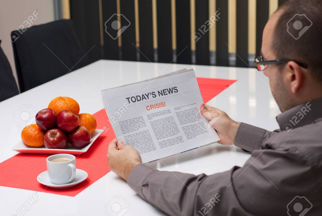 Man reading crisis article in the newspaper at home