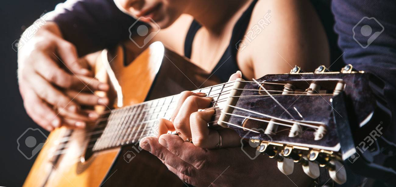 blurred man's hands playing acoustic guitar, and teaching guitar, too softa girl to play guitar. Black concert studio background. - 53361793
