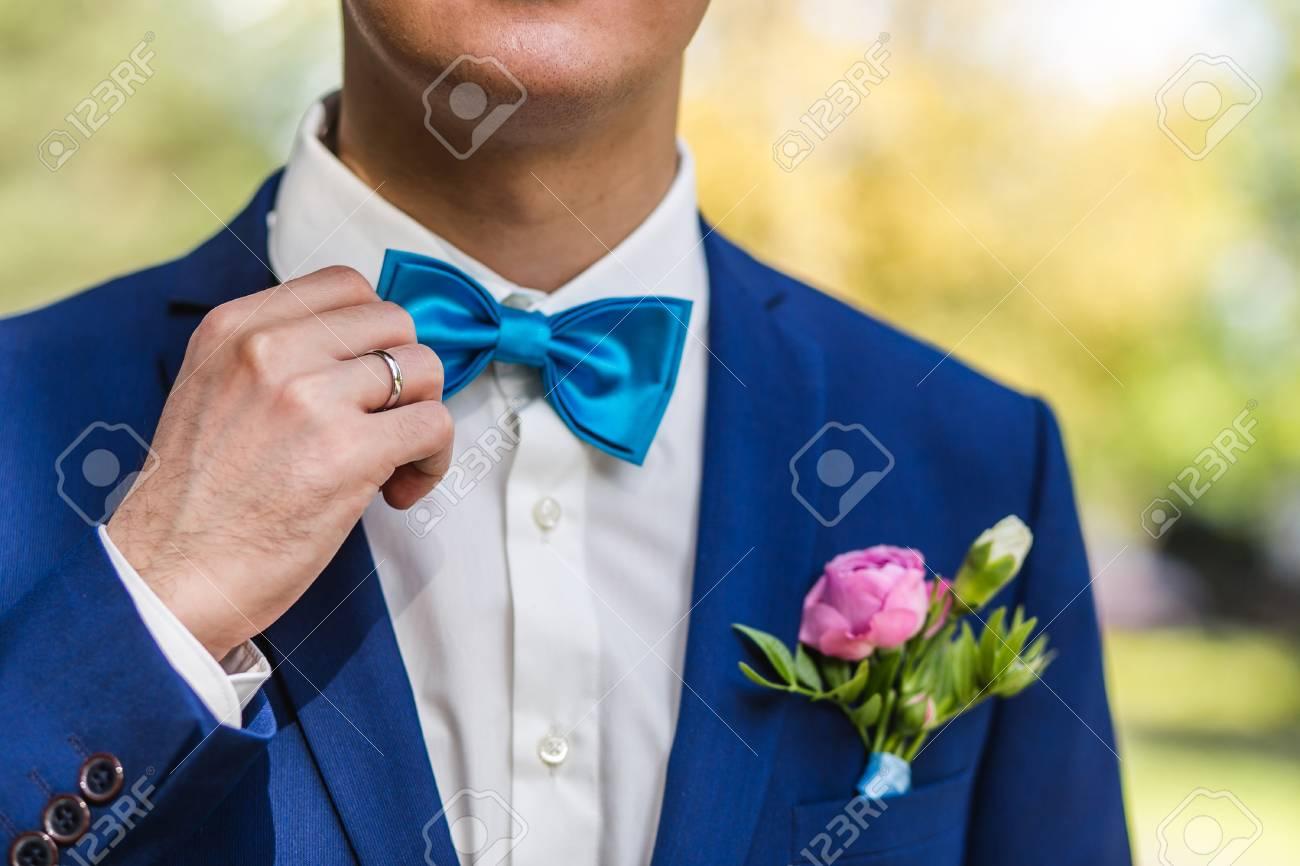 codes promo Quantité limitée prix de gros Le marié sstraightens une cravate. Gros plan du marié dans le parc le jour  de leur mariage.