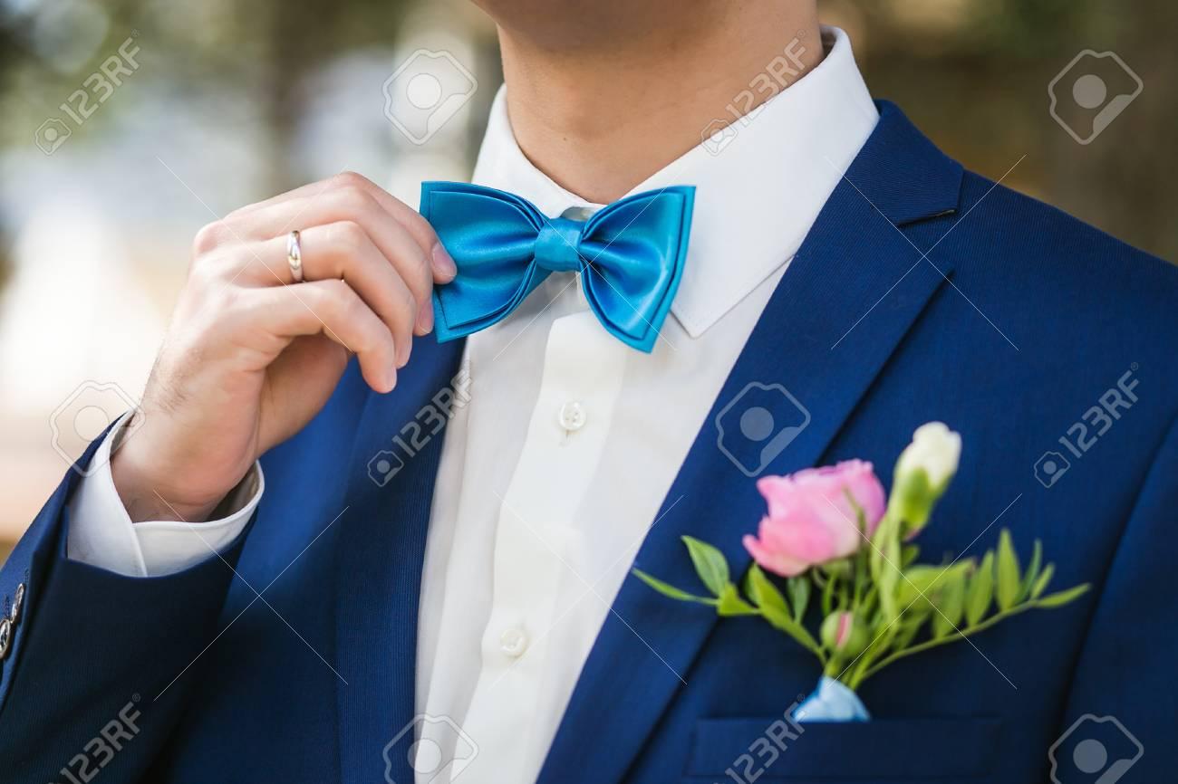 coupe classique remise chaude hot-vente authentique Le marié élégant redresse une cravate. Gros plan du marié vêtu d'une veste  bleue et d'une chemise blanche au parc le jour de leur mariage.