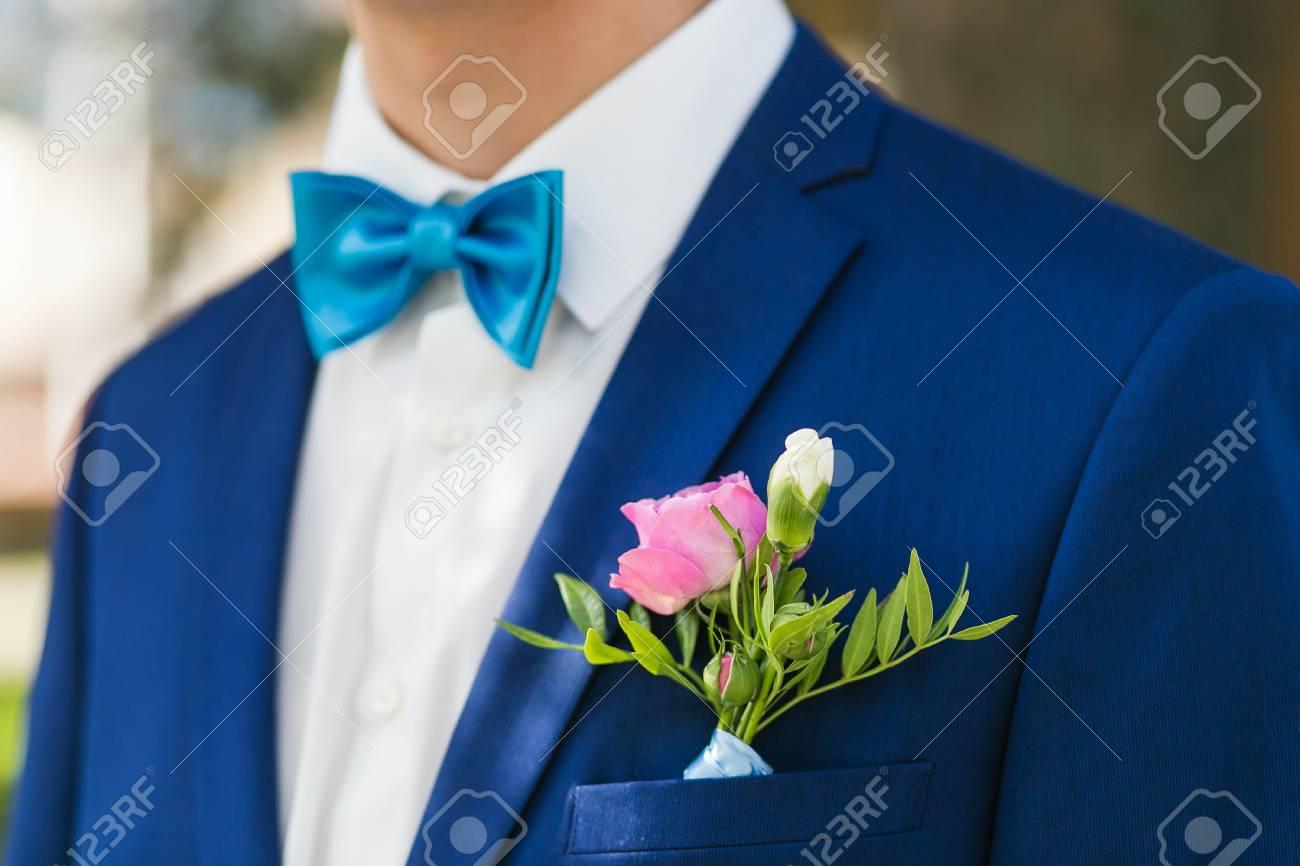 El novio elegante del primer arropado en chaqueta azul y la camisa blanca en el parque el día de su boda. Enfoque en rosa boutonniere