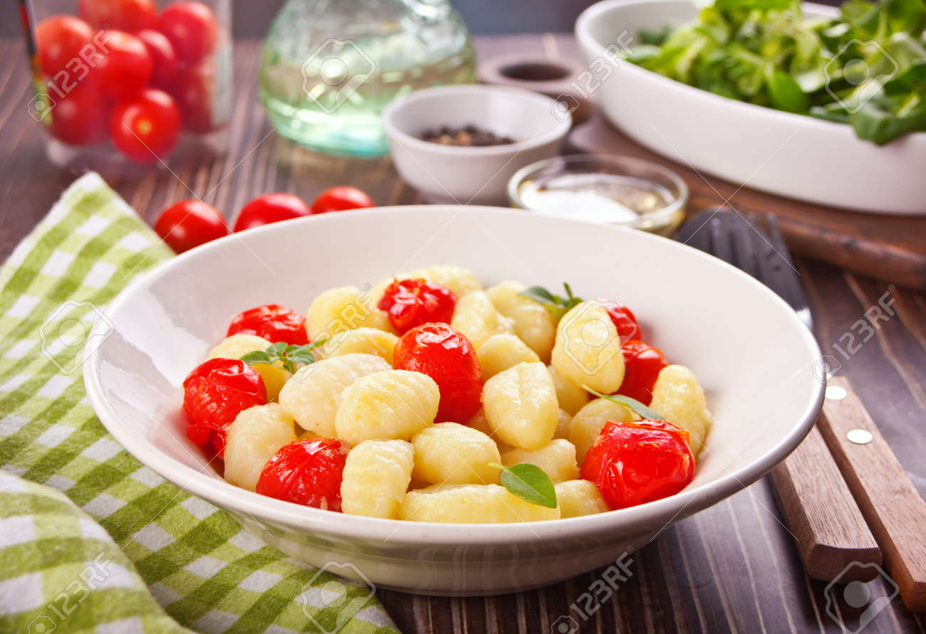 Homemade Italian gnocchi with tomato cherry on the wooden table - 168449068