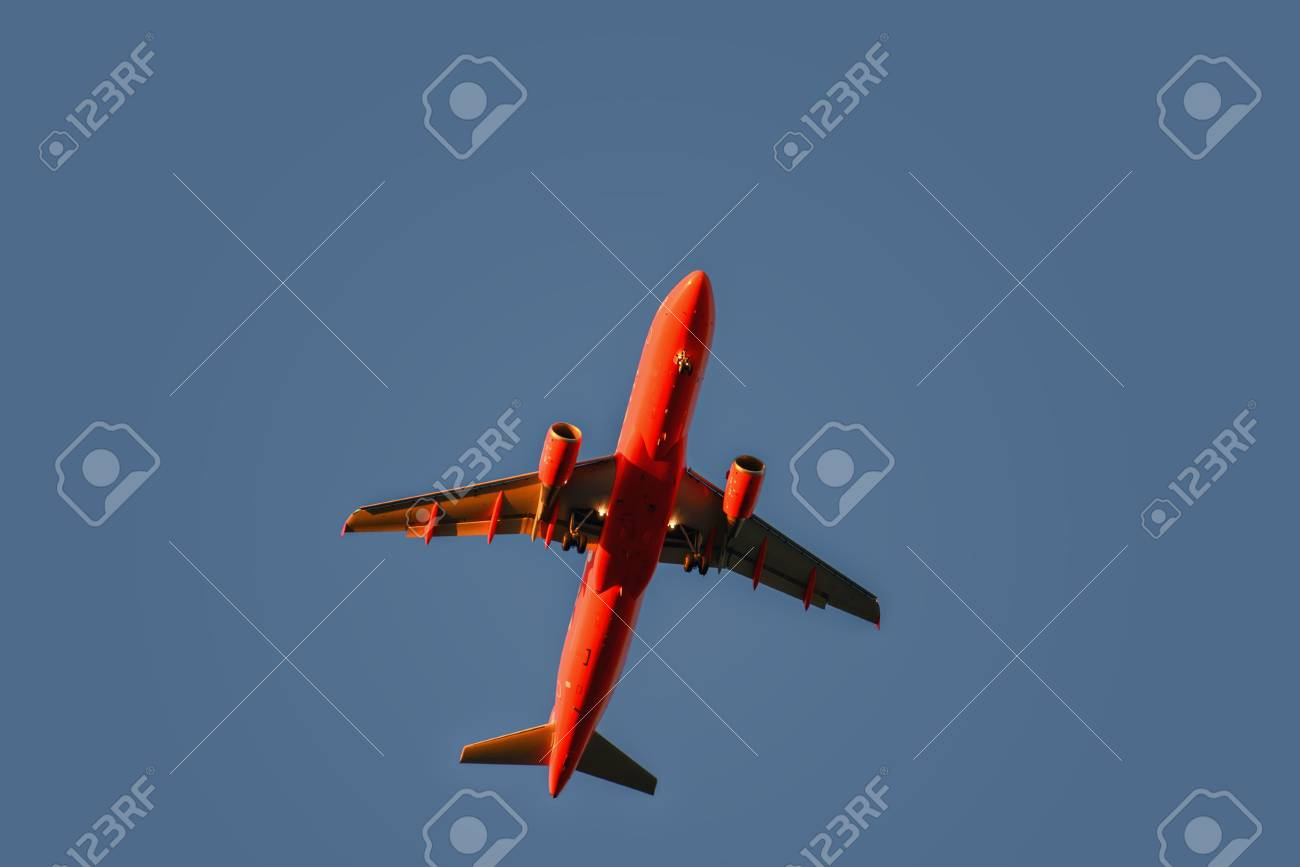 Red airplane in the sky at sunset with landing lights