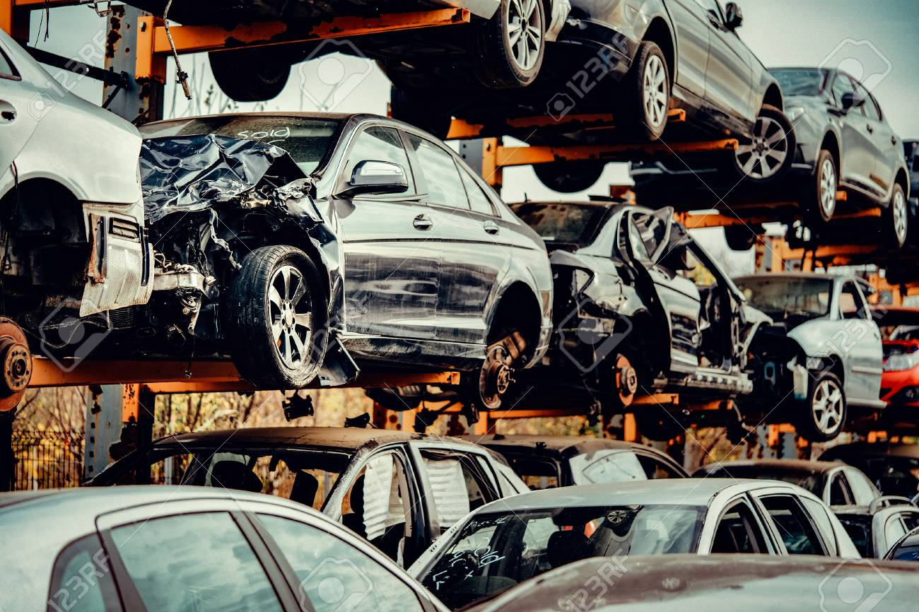Damaged cars waiting in a scrapyard to be recycled or used for spare part - 113845137