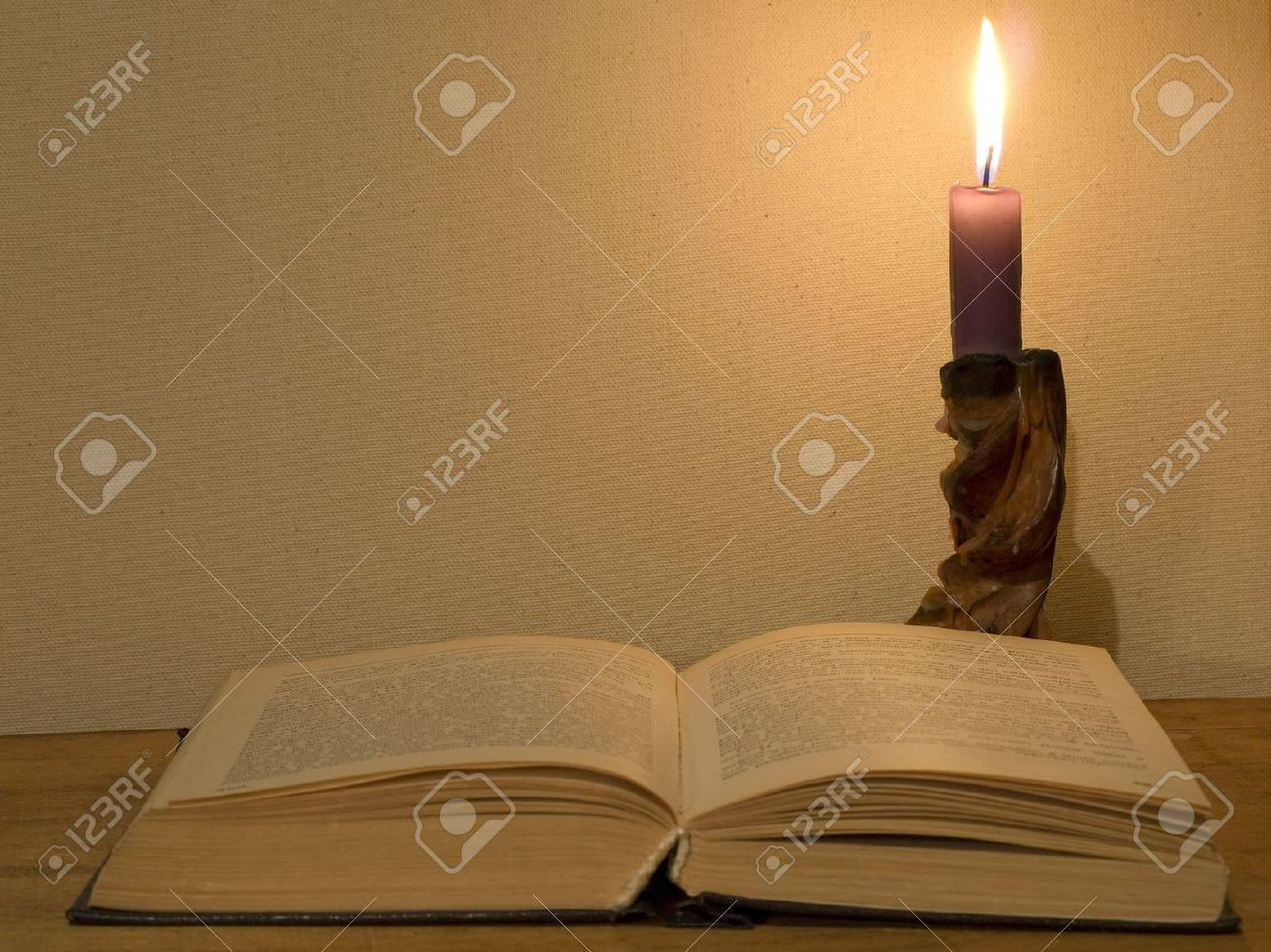 Old open book and  glowing candle on a wooden table. Stock Photo - 11511172