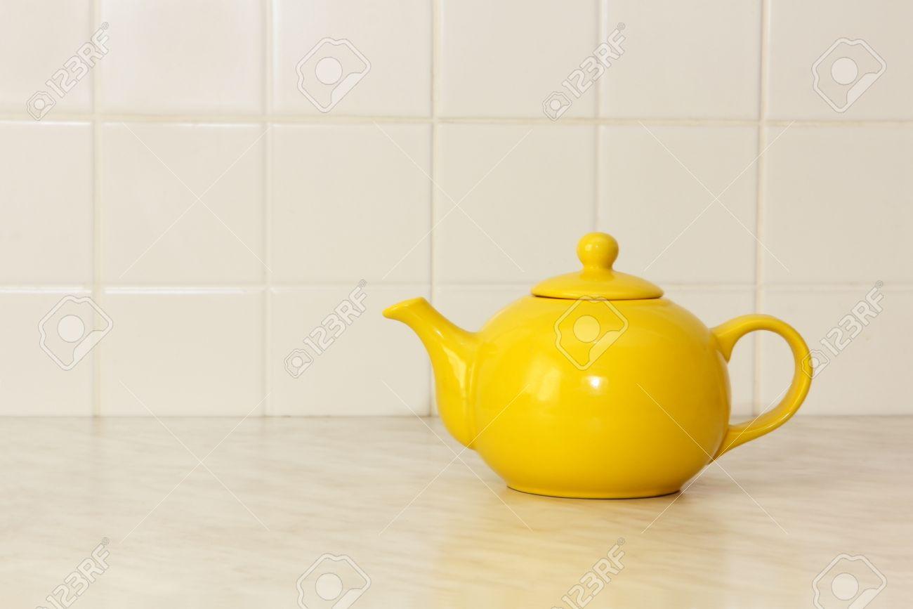 Yellow ceramic teapot on white kitchen table and ceramic tile stock photo yellow ceramic teapot on white kitchen table and ceramic tile background dailygadgetfo Choice Image