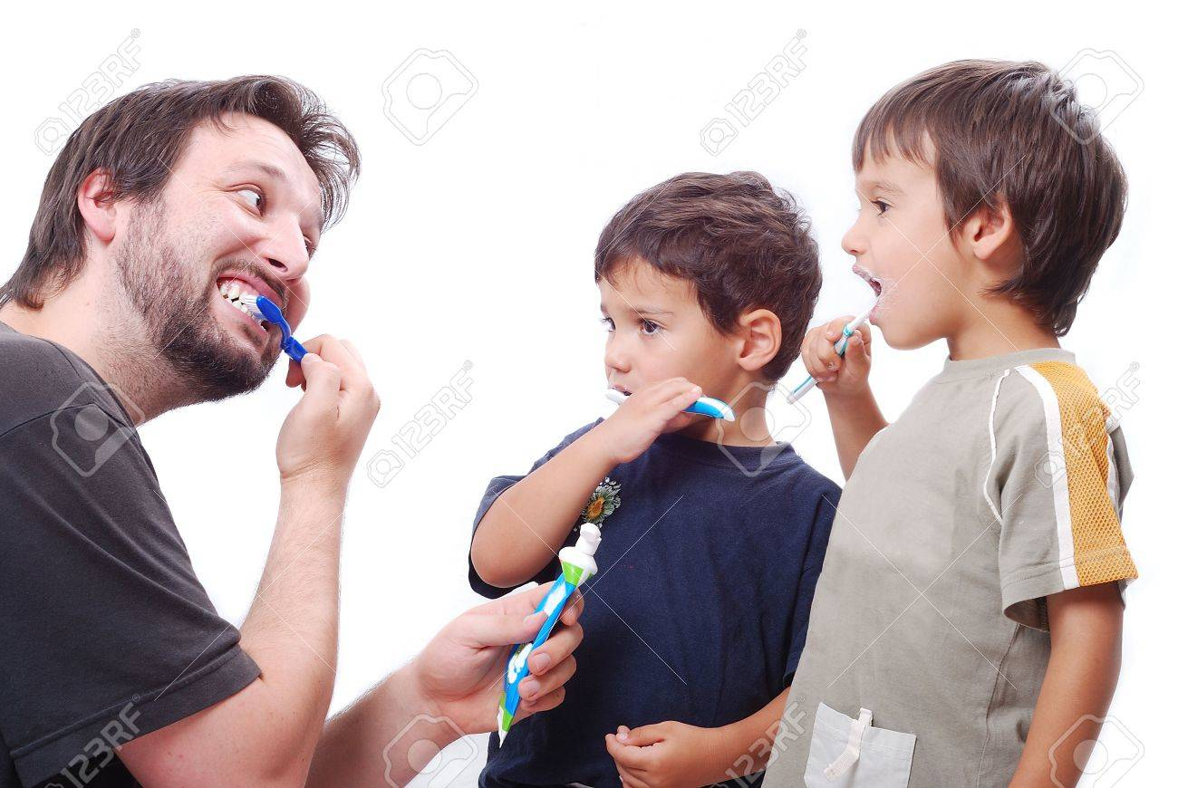 Father is teaching his son hot to clean the teeth properly Stock Photo - 5142527