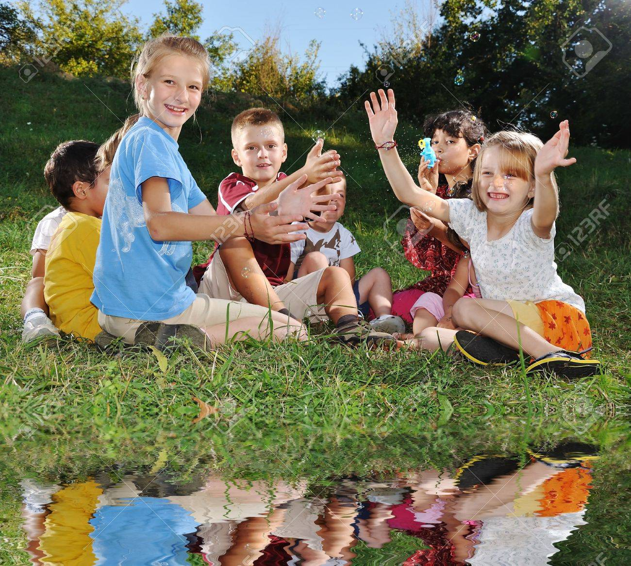 Happy group of children on lake Stock Photo - 6516515