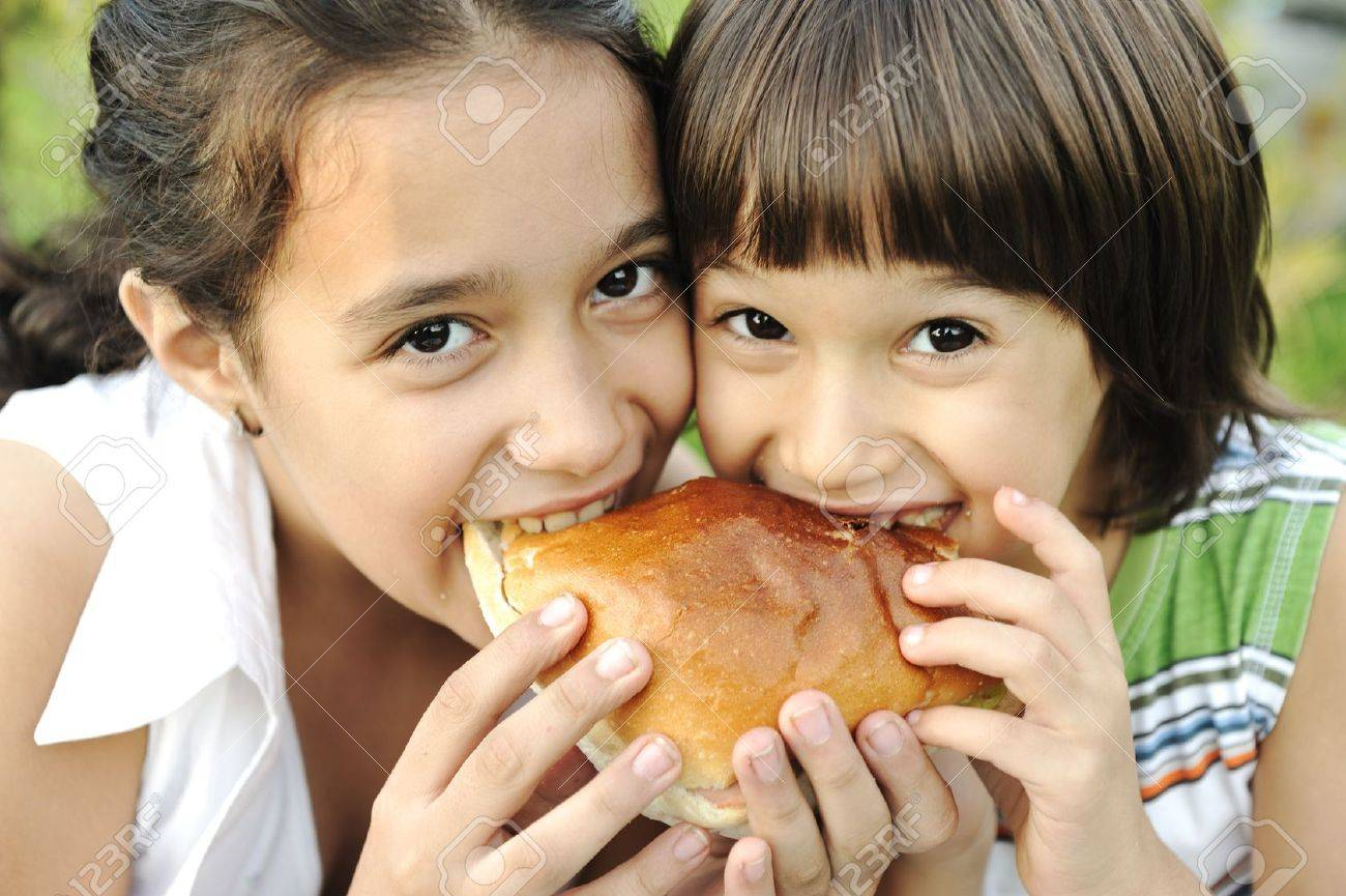 Closeup of two children eating sandwich in nature together, healthy food, care and love Stock Photo - 8120338