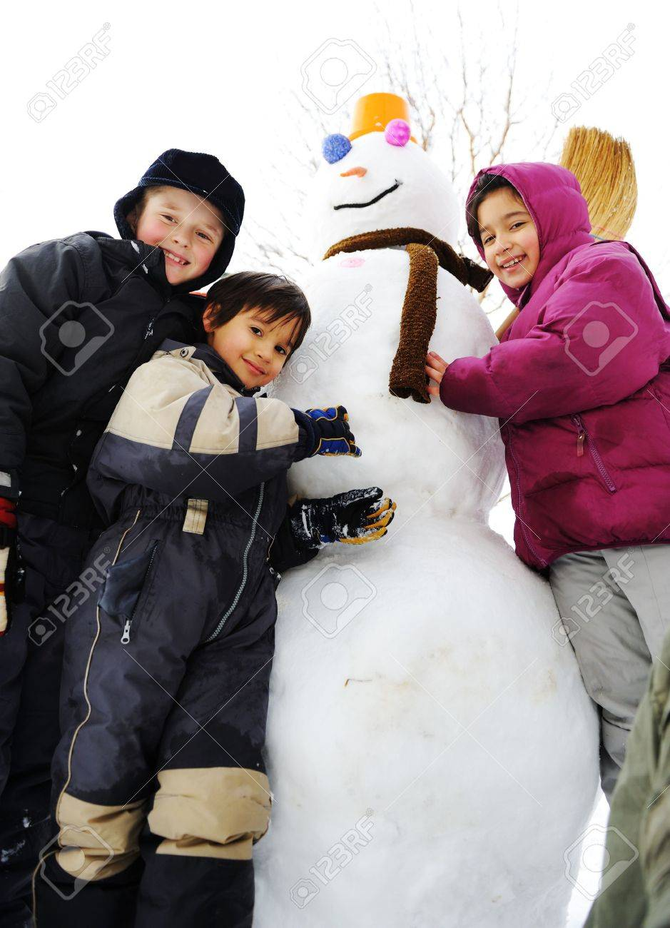 Group of children playing happily in snow making snowman, winter season Stock Photo - 8120322