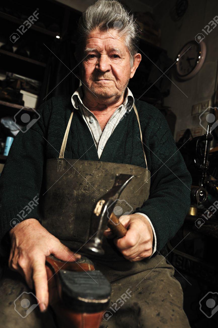 Elderly man, shoemaker repairing old shoe in his workshop - 8818848