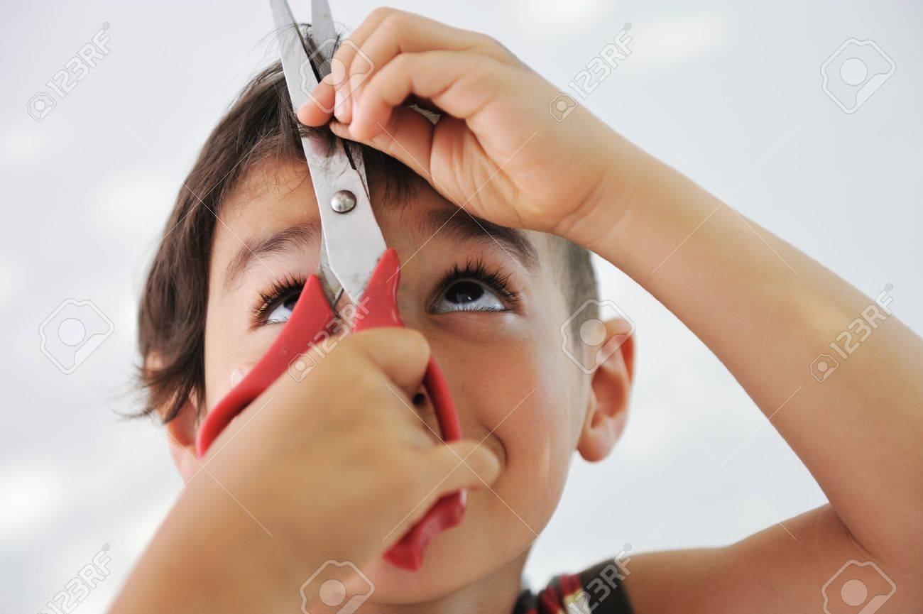 Kid cutting hair to himself with scissors, funny look Stock Photo - 10290230
