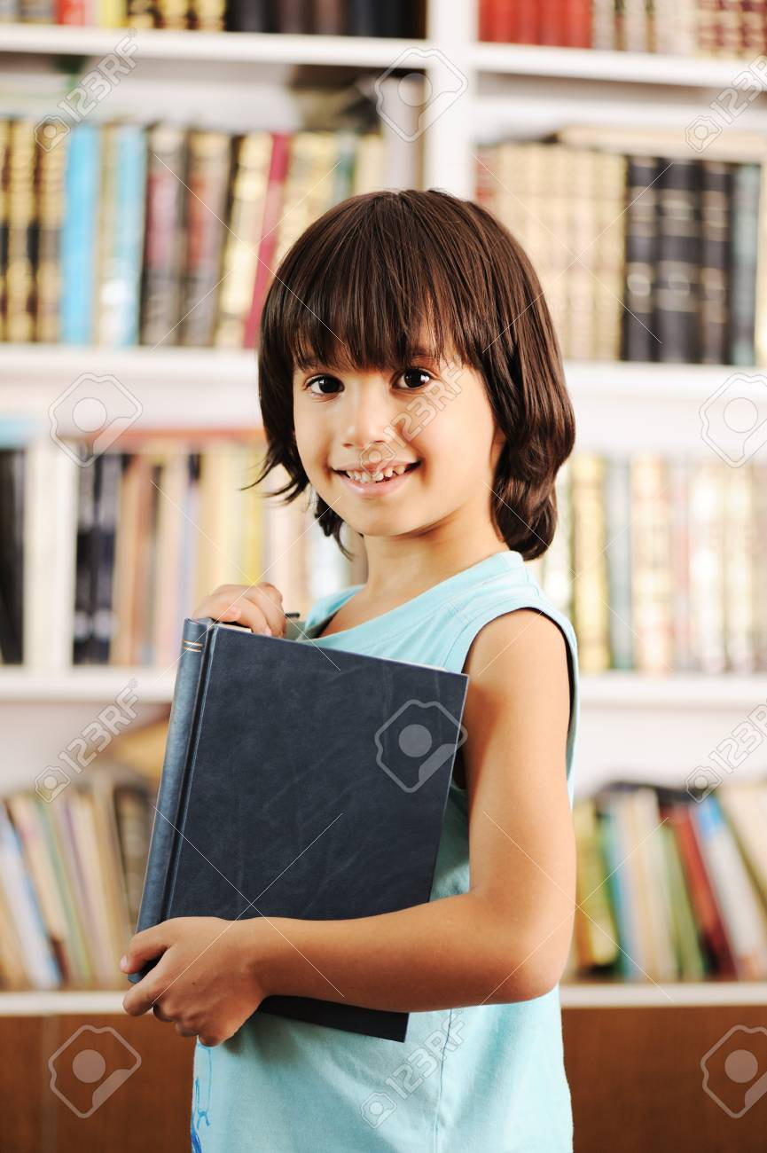 Kid with book in library Stock Photo - 10680834