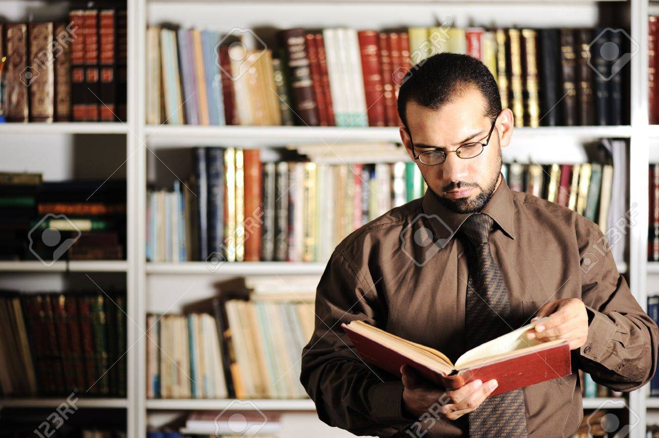 Young man reading book in library Stock Photo - 10680844