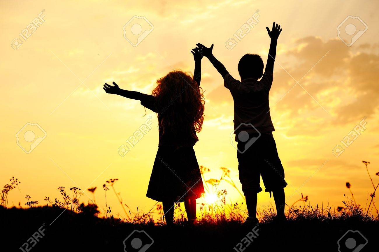 Silhouette, group of happy children playing on meadow, sunset, summertime Stock Photo - 10873884