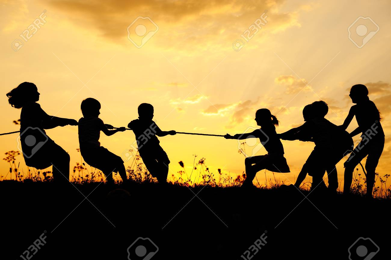 Silhouette, group of happy children playing on meadow, sunset, summertime Stock Photo - 10873924