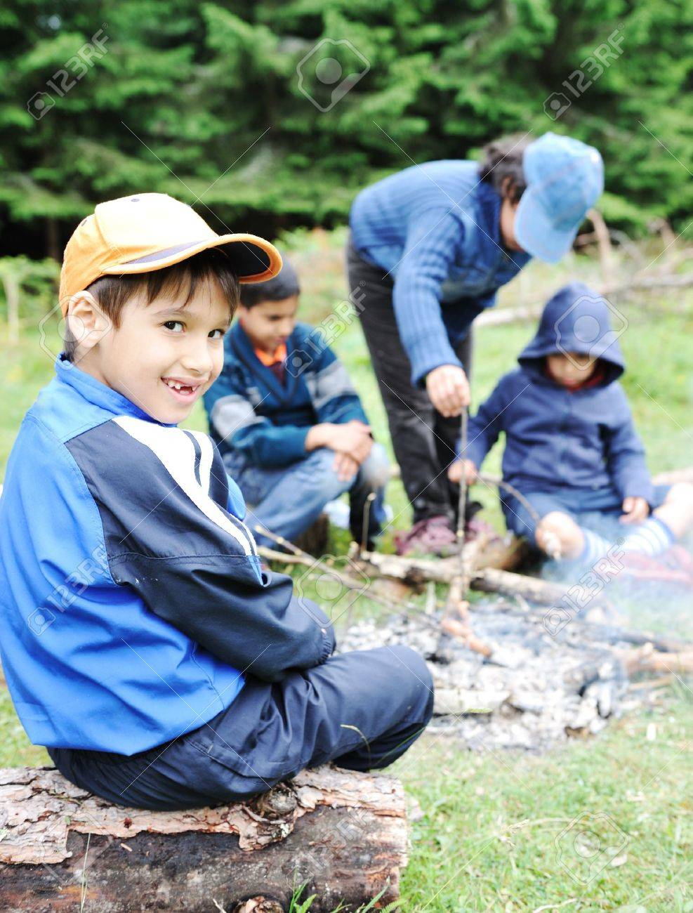 Barbecue in nature, group of children  preparing sausages on fire Stock Photo - 11176884