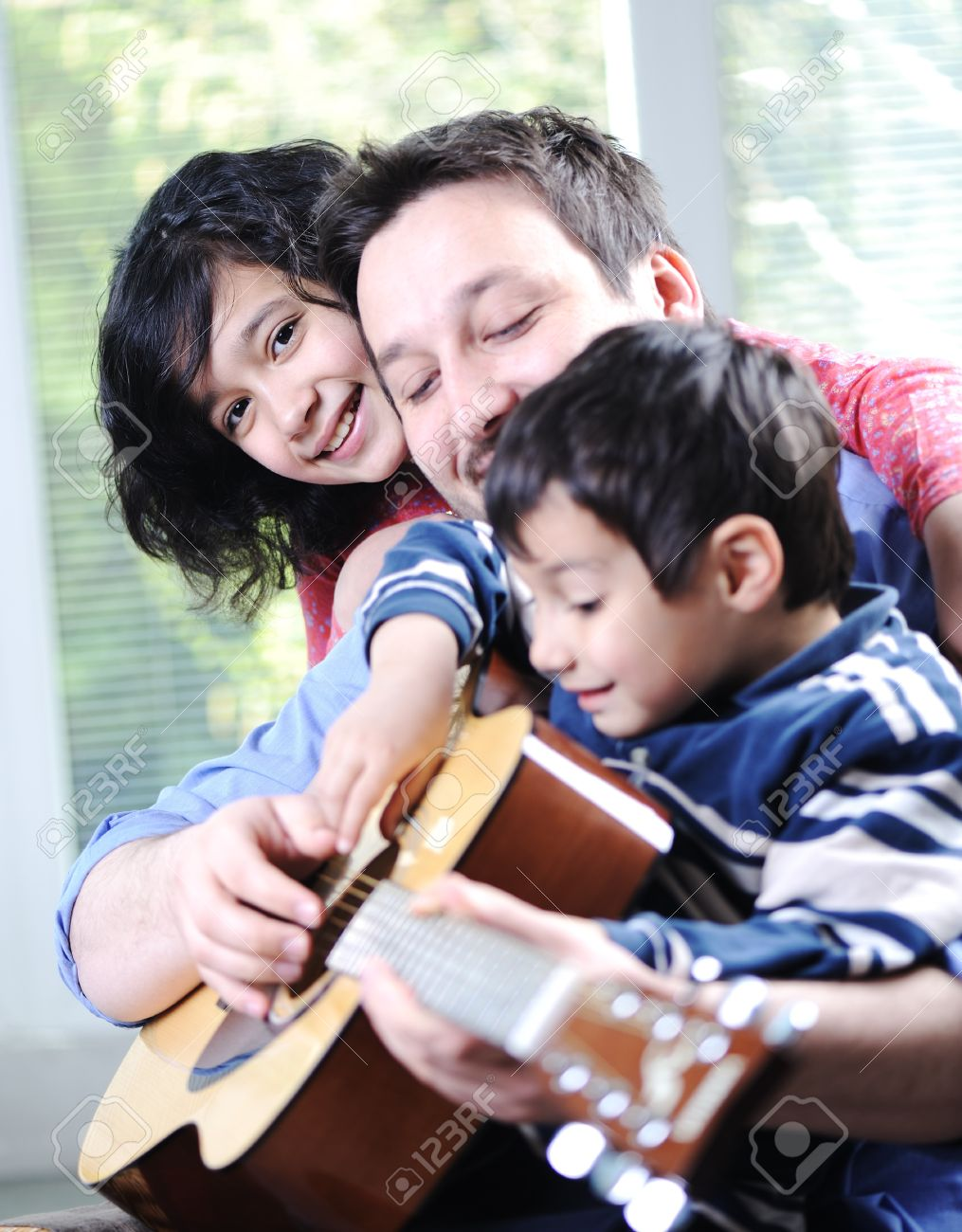 Happy family playing guitar together at home Stock Photo - 13665132