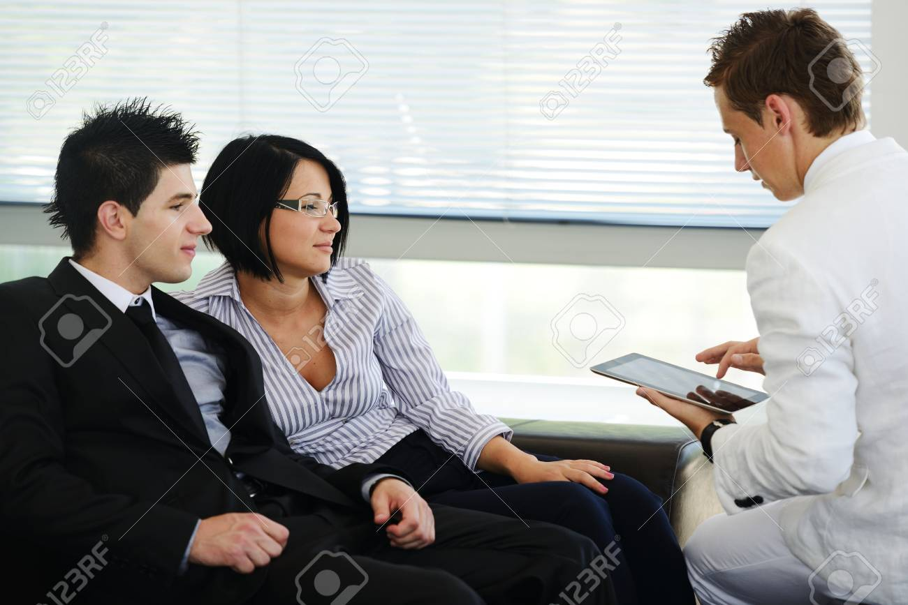 Portrait of modern couple talking to manager while discussing conditions of mortgage using tablet Stock Photo - 19265851
