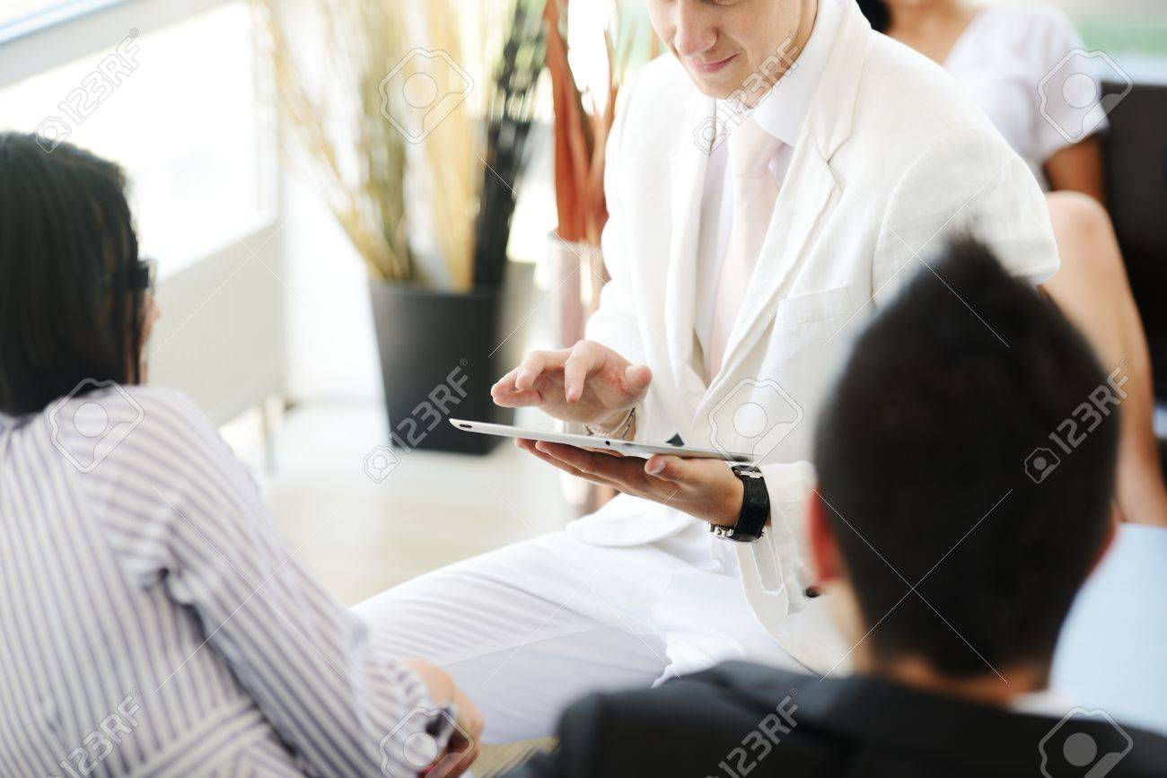 Portrait of modern couple talking to manager while discussing conditions of mortgage using tablet Stock Photo - 19265485