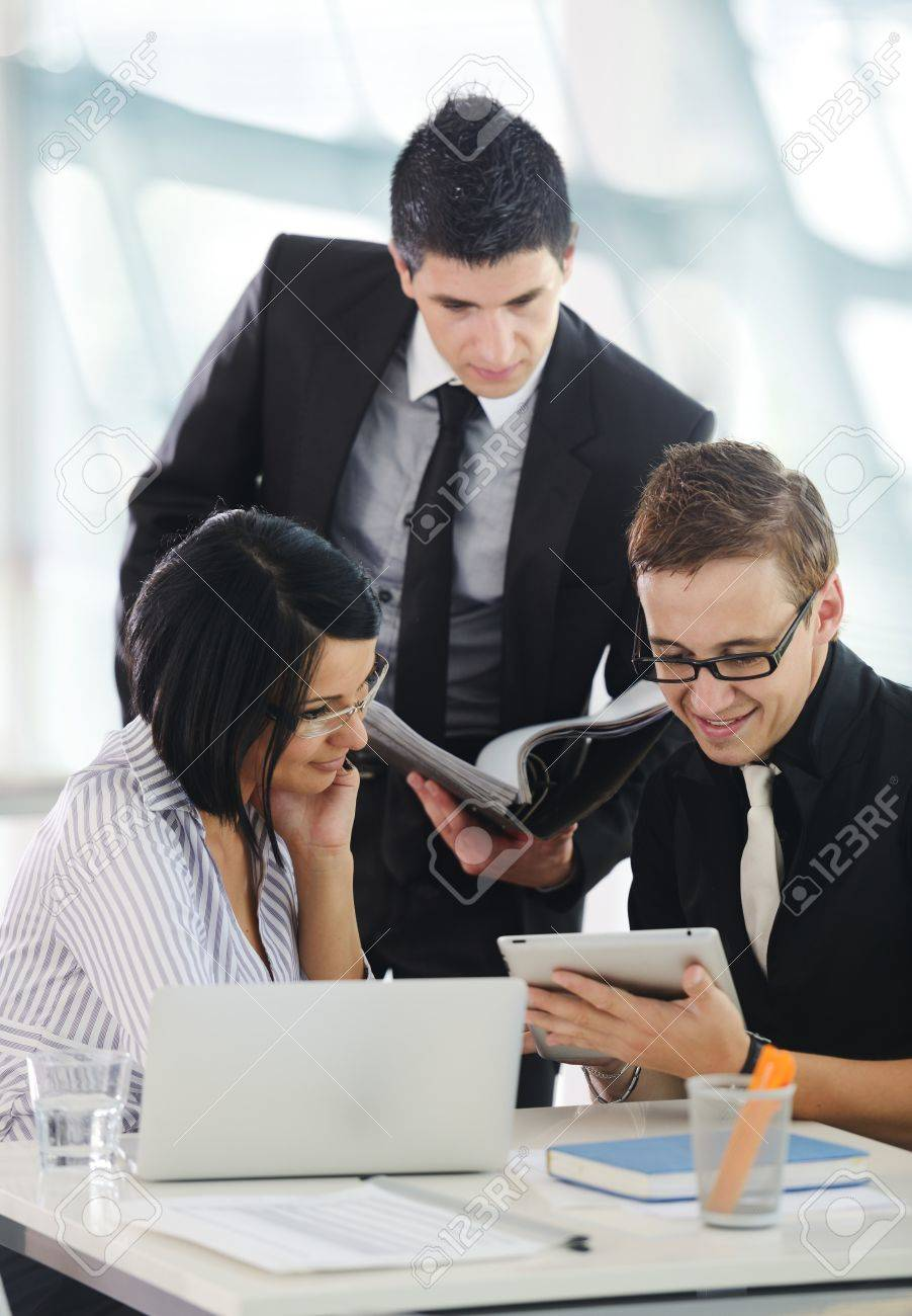 Three business people working at office with paperwork using tablet and laptop Stock Photo - 19311073