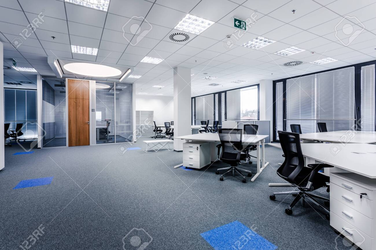 Part of ordinary office room decorated in modern style with meeting room,large windows with blinds,carpeting,ventilation,escape signs,white furniture (tables, shelves, drawers) and dark office chairs. - 136488143