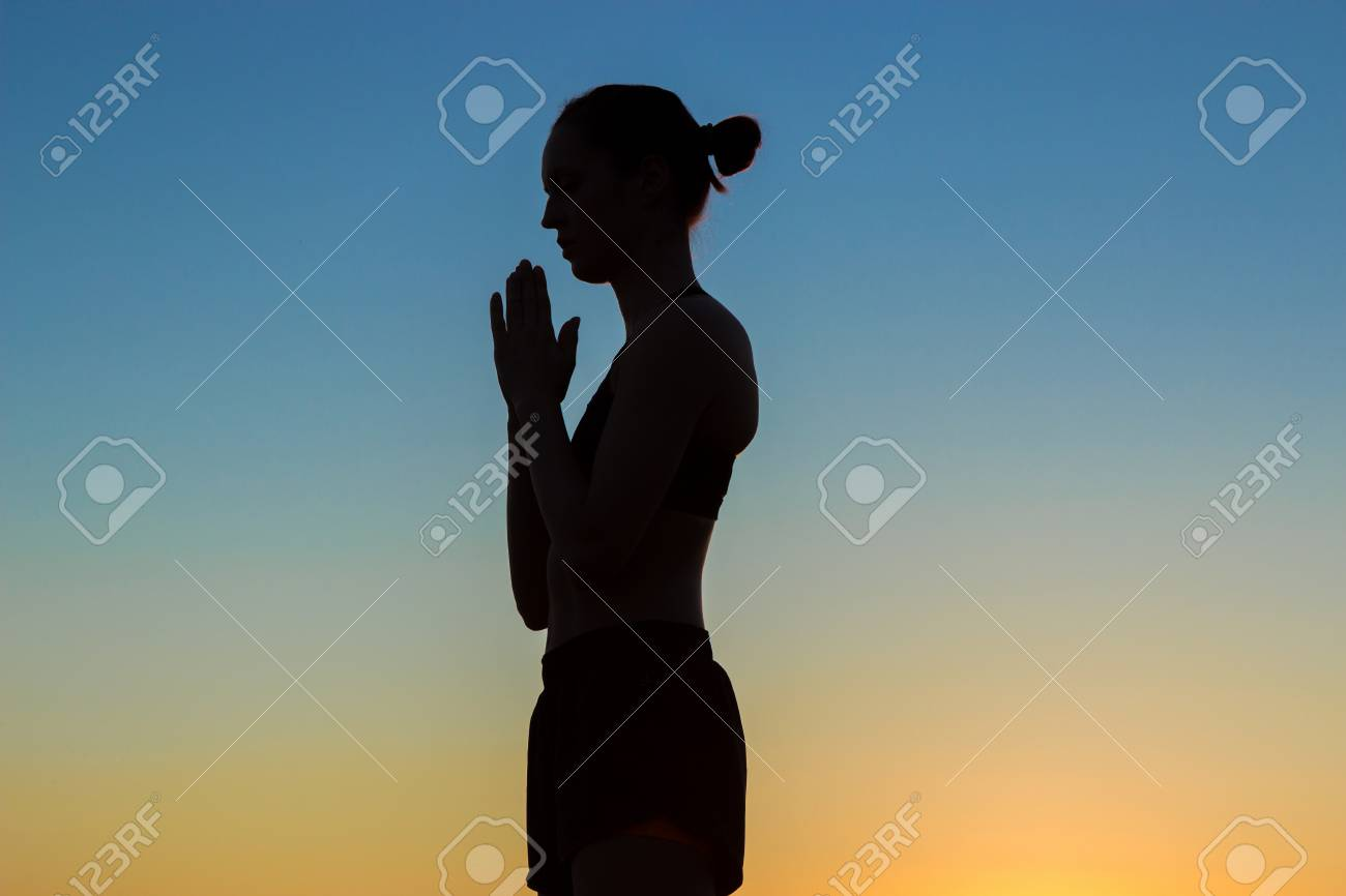 Sporty Woman Practicing Yoga In The Park At Sunset Making Hand