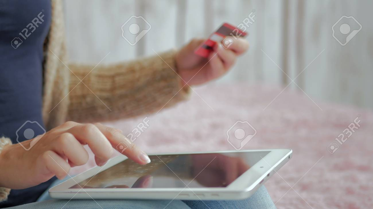 b0087f27e Stock Photo - Young woman buying goods from the internet and entering  number security code from credit card on digital tablet. Online