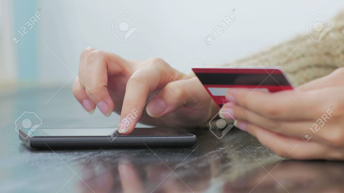 d0a33365c Stock Photo - Young woman buying goods from the internet and entering  number security code from credit card on smartphone. Online