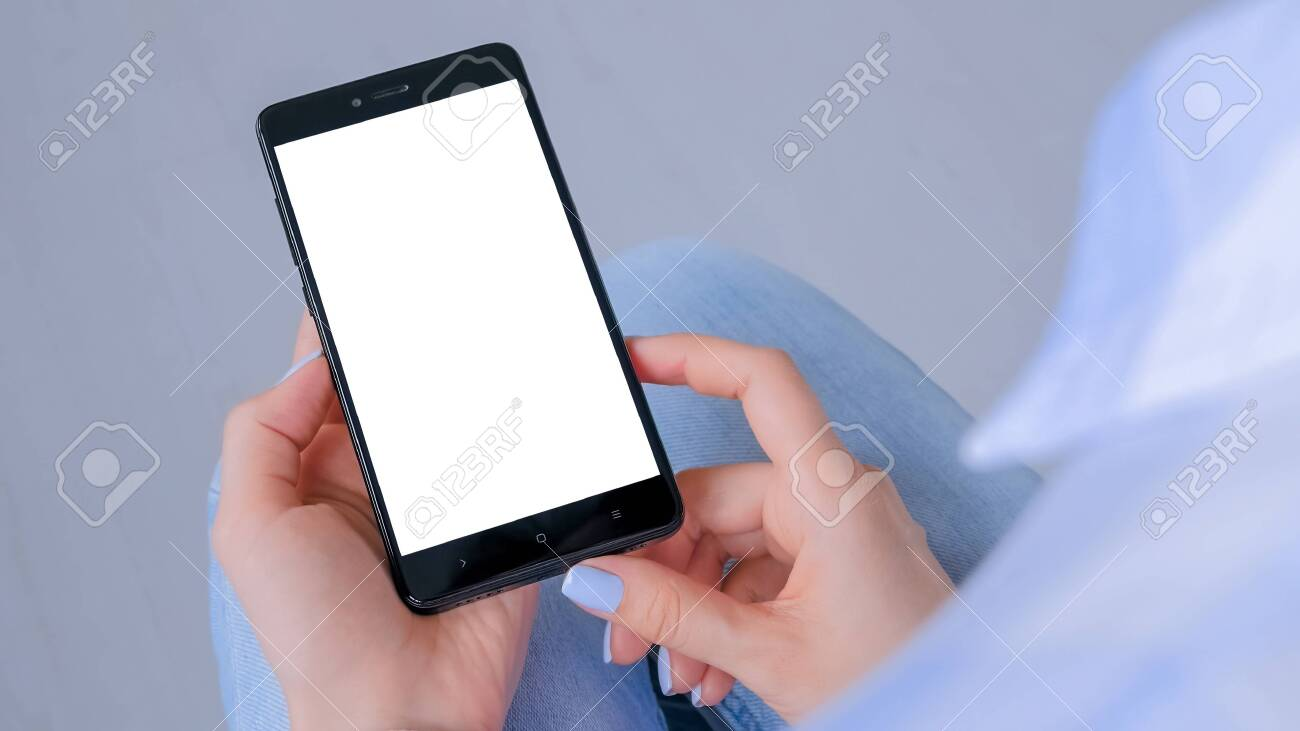Over shoulder view: woman hands holding black smartphone with white blank screen in home interior. Mock up, copyspace, template, entertainment and technology concept - 146058276
