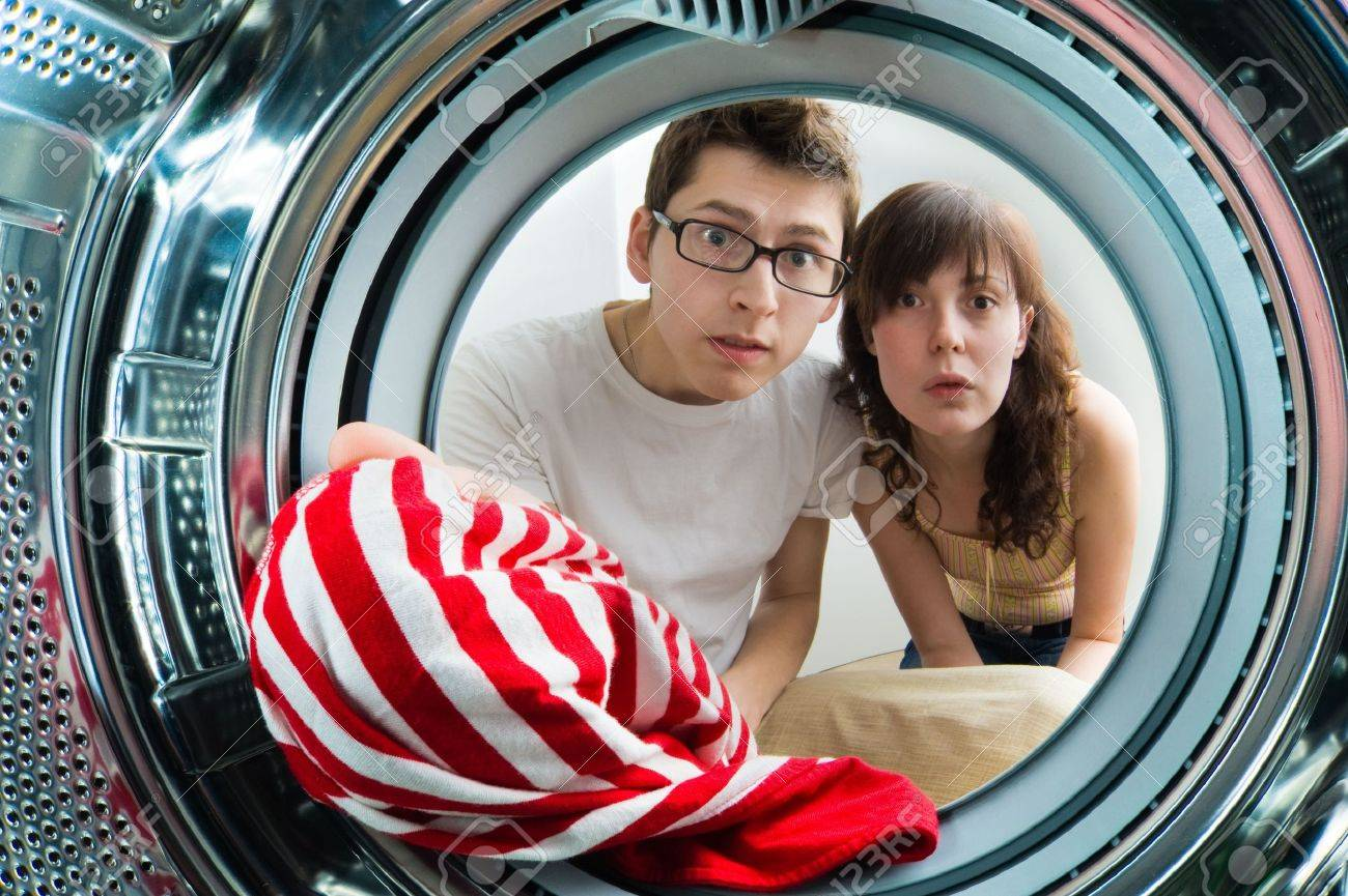 Funny couple loading clothes to washing machine. From inside the washing machine view. Stock Photo - 6561096