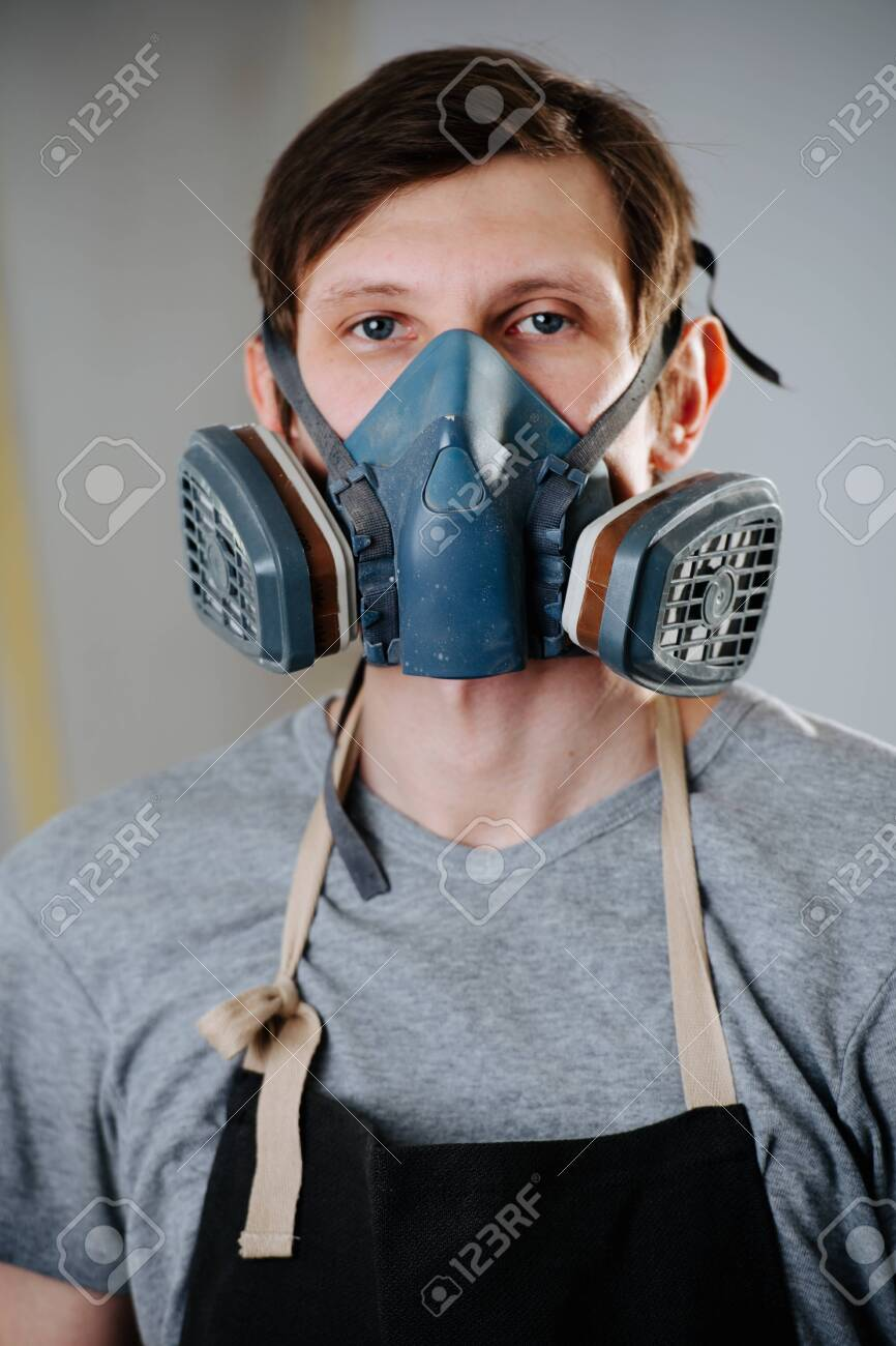 Close up portrait of working handsome slim middle aged brunet carpenter in respirator. He is making furniture on order in a workshop. Standing still for a portrait between worksteps. Painting room. - 121248025