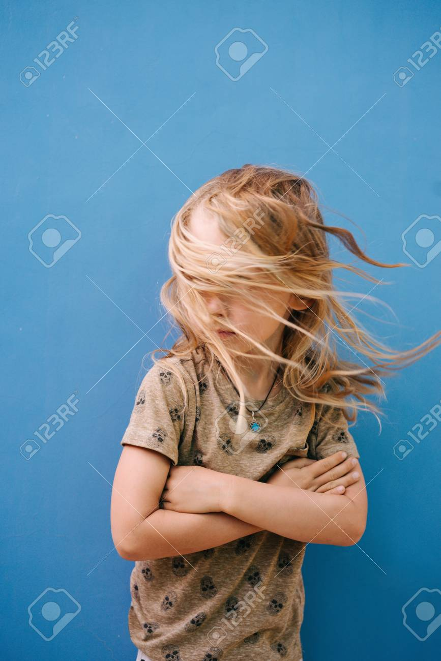 Little boy with long blond hair in white T-shirt posing in front of house wall. His face is completely covered by messy tangled uncombed after swim windy hair. Hands crossed on chest. - 122197901