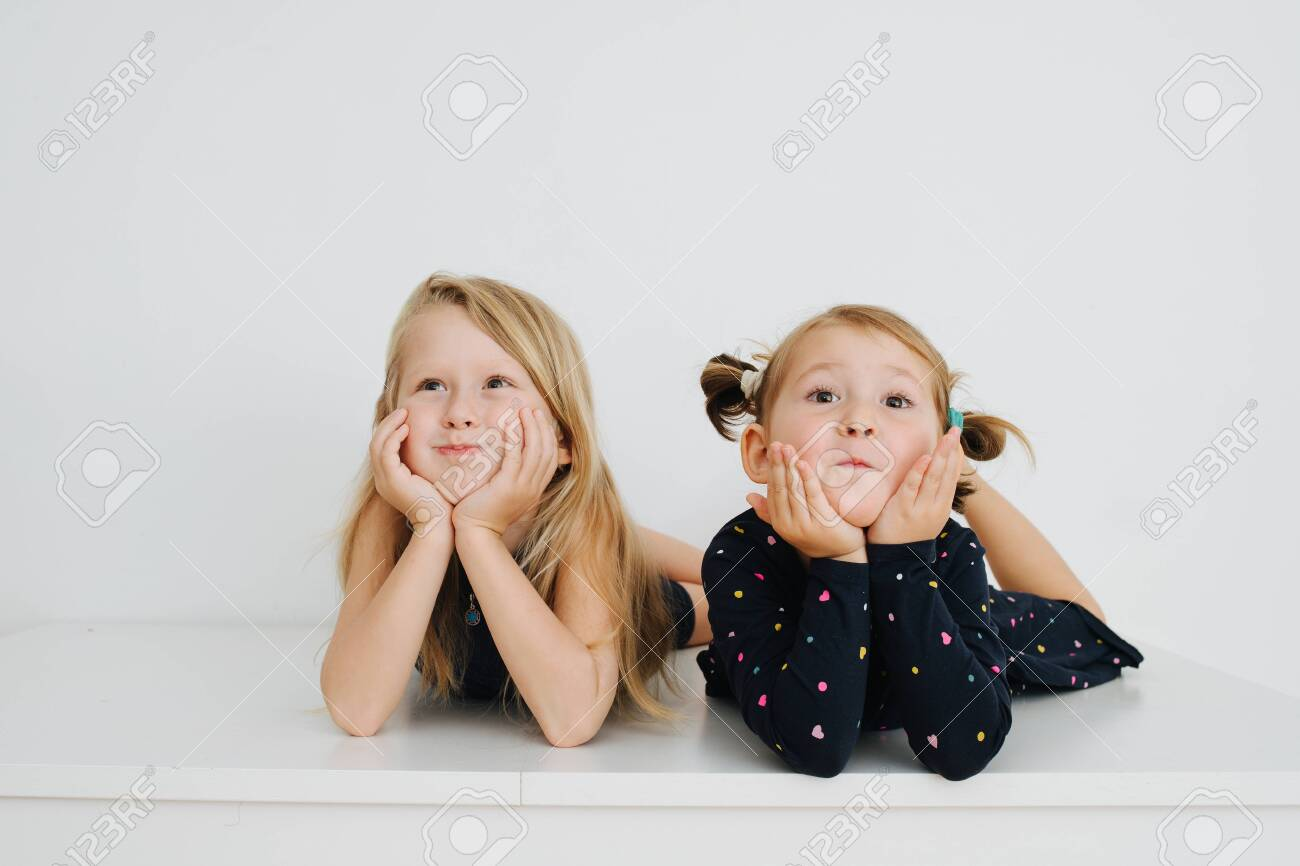 Adorable little barefoot siblings lying on a table with their feet up. Over white wall. Inflating their cheeks, leaning on hands, making cute faces for the camera. Both in nightware. - 143650456