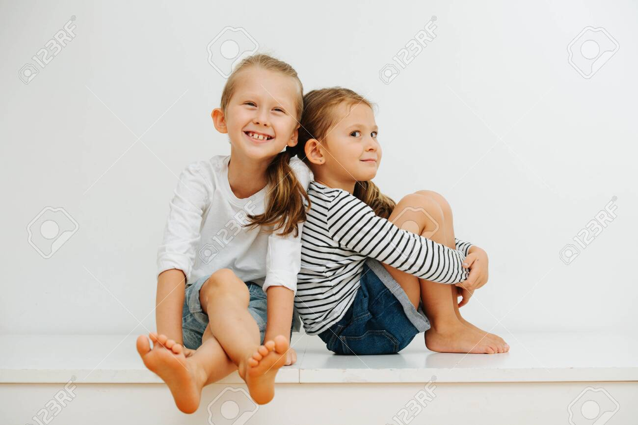 Funny little barefoot siblings sitting on a table with their legs up. Over white wall. Both wearing jeans shorts and long-sleeves. Boy is cheerful and girl is giving a perky look for camera. - 143650465