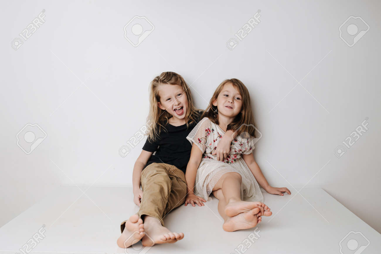 Naughty boy hugs girl, she leans away. Siblings sitting together on a table. - 159990096