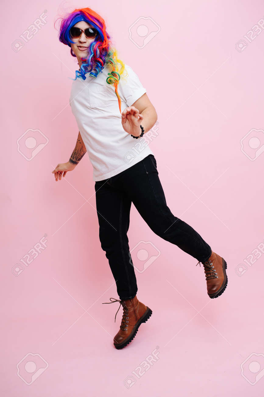 Feminine man playing girl, jumping around and playing cute. He is wearing rainbow colored wig and sunglasses. Over pink background - 167388396